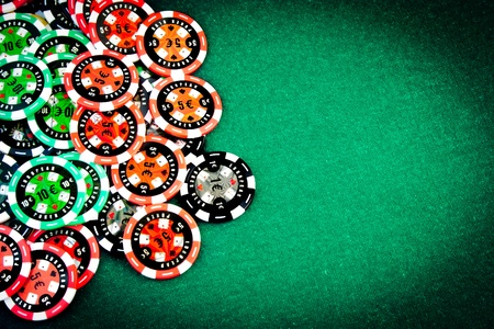 money risk: Gambling chips in upper left corner of a green fabric background