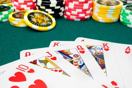 royal flush and unfocused gambling chips of a green fabric background
