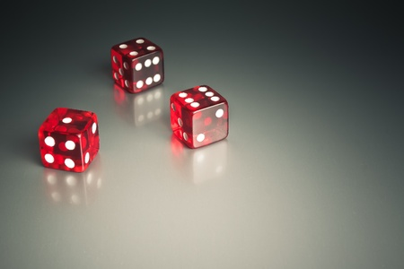 three red dice in the corner on a silver gaming table