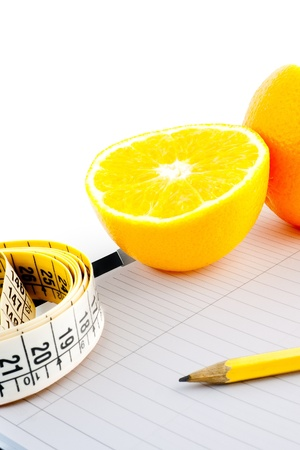 detail an orange with a measuring tape on notepad
