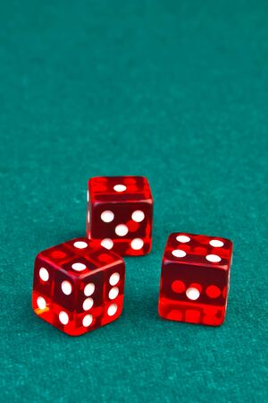 detail of three reds dice on green fabric background  photo