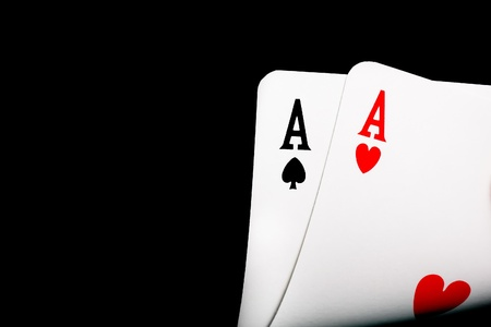 ace of clubs: detail of winning aces on black background