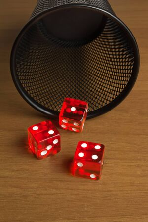 red dice  near a container on old wood table  photo