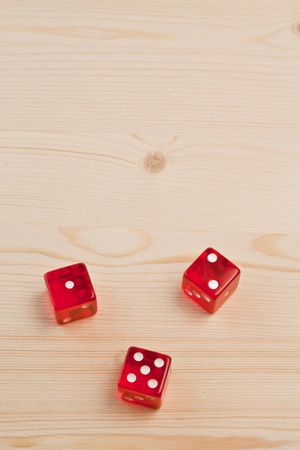 top view of gaming red dice on light wood with space for text photo