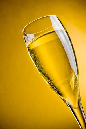 close up of champagne in a glass on golden background with space for text photo