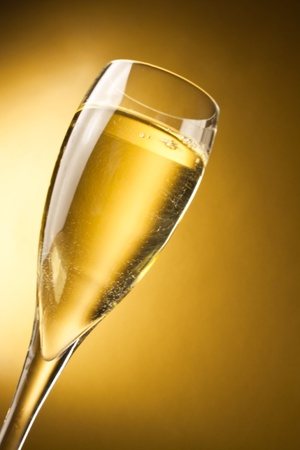 a champagne flute against a golden background with space for text photo