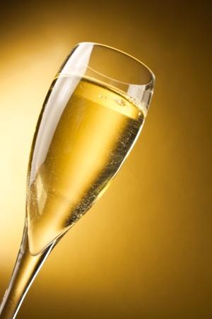 ett champagneglas mot en gyllene bakgrund med utrymme för text