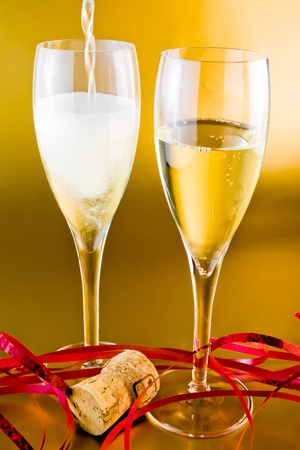 close up a pair of champagne flutes with decoration on golden background photo