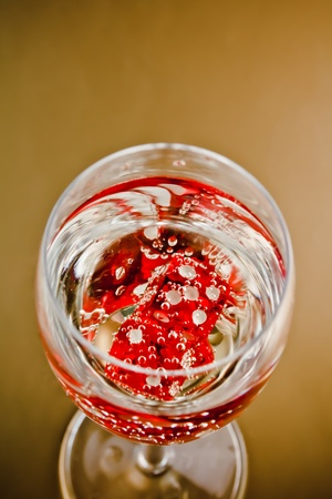 top view of red dice in a champagne glass on golden background photo