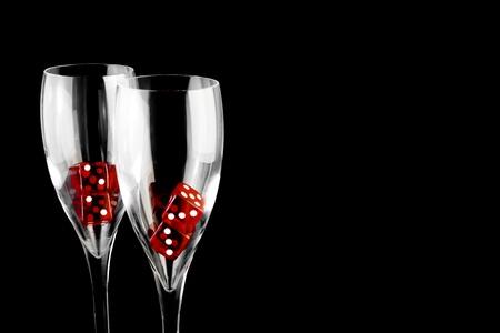 fichas casino: dados rojos en un vaso de champ�n sobre fondo negro Foto de archivo
