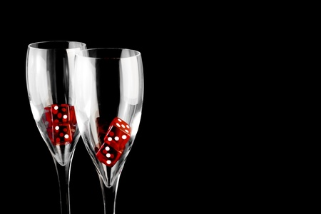 red dice in a champagne glass on black background