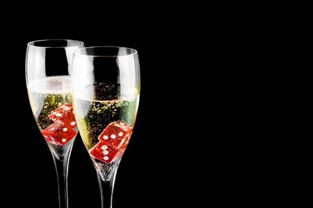 röda tärningarna i ett champagneglas på svart bakgrund