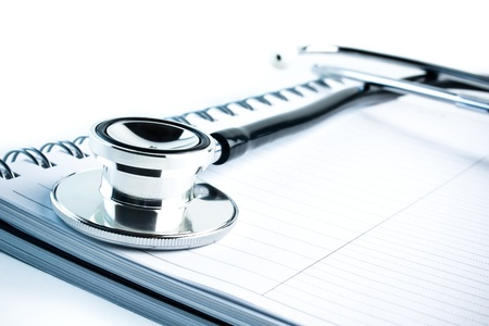 detail of medical stethoscope with blue tint on notebook