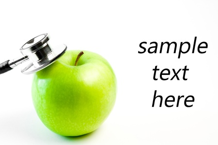 detail of medical stethoscope and apple on a white background with space for text Stockfoto