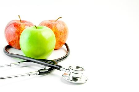 estetoscopio corazon: detalle de estetoscopio m�dico y tres manzanas en el fondo blanco con espacio para texto Foto de archivo