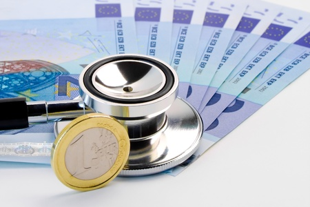 detail of stethoscope on banknote near euro coin on white background photo