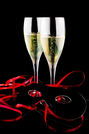 two flutes with champagne near a carnival mask on black background Stock Photo