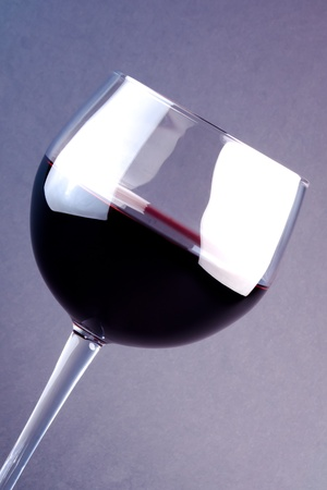 a glass of wine on a light purple background photo