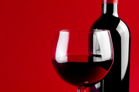 red wine glass and bottle on red background with space for the text photo