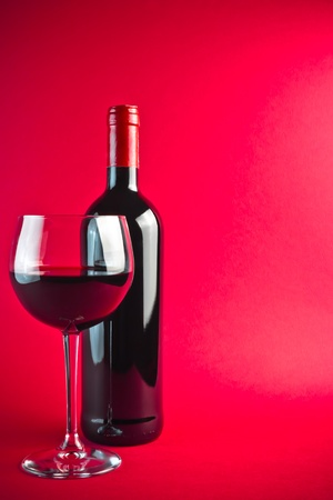 bottle with red wine and glass on red background photo