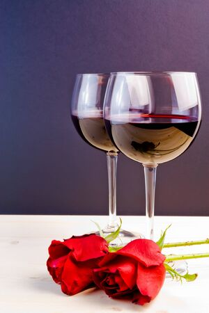 glasses of wine near red roses on old wood photo