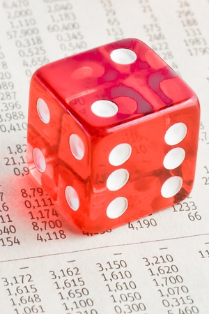 detail of one red dice on the financial newspaper photo