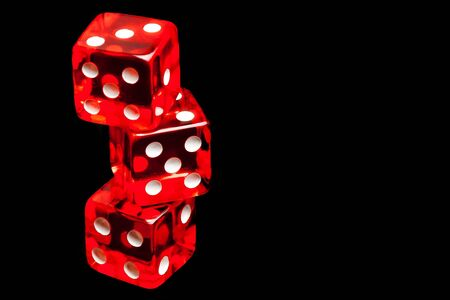 money risk: three red dice on black background with space for text Stock Photo