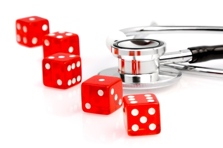 red dice near stethoscope on the white table