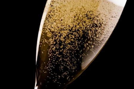 detalj av en flöjt med mycket champagne guld bubblar på svart bakgrund