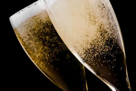 detalj av två flöjter med champagne guld bubblar på svart bakgrund