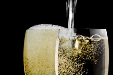 sektglas: volle Gl�ser Champagner und ein gegen schwarzen Hintergrund gef�llt