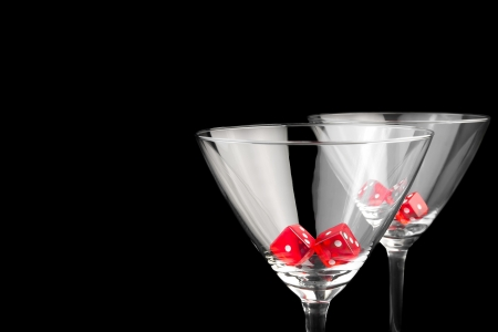 red dice in two cocktail glasses on black background with space for text Reklamní fotografie