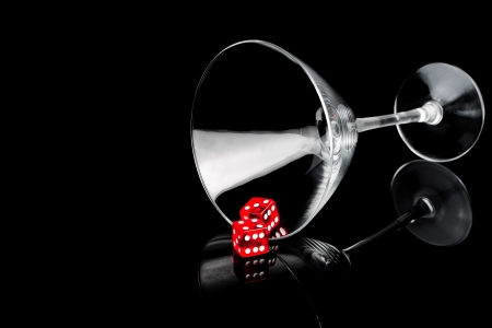 two red dice in a cocktail glass on black background with space for text