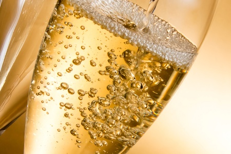 empty glasses of champagne and one being filled against golden background