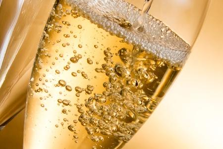 tomma glas champagne och en fylls mot gyllene bakgrund Stockfoto