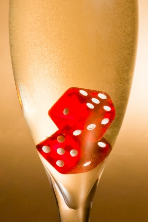 detail of a flute with inside red dice and gold bubbles on golden background photo