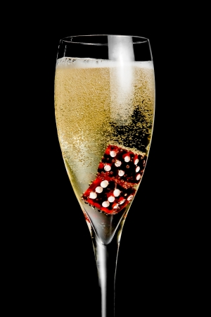 champagne flute with golden bubbles and red dice on black background