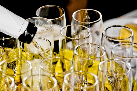 champagne flutes: closeup of group of flutes of champagne on festive table and one is being filled