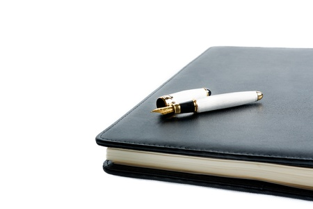 notebook and pen in composition on white background photo