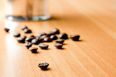 coffeepot: detail of coffee bean with unfocused coffeepot  on wood background Stock Photo