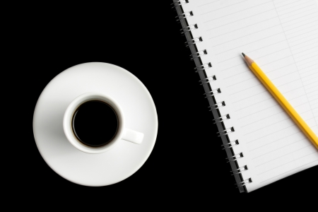 cup of black coffee with notepad and pencil on black table photo