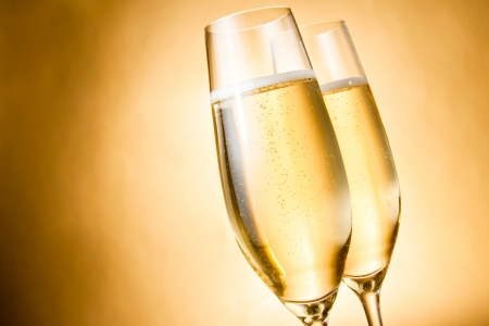 two glasses of champagne with golden bubbles against golden background