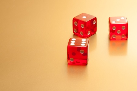 three red dice on golden background with space for text photo