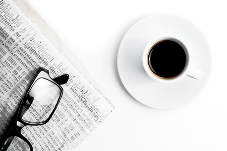 exceeds: top of view of coffee near financial newspaper and glasses
