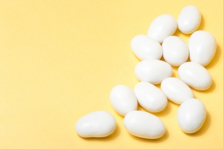 organza:  white jordan almonds on yellow background with space for text