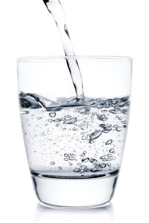 fyller ett glas med att hälla vatten på vit bakgrund