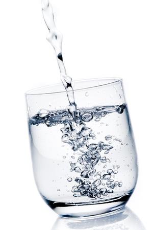 fyller ett glas med rent vatten på vit bakgrund Stockfoto