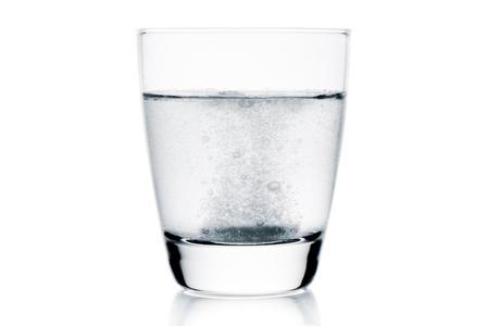 medicinsk tablett föll i vattnet med bubblor på vit bakgrund