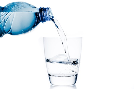 pouring a glass with water trough little blue bottle and space for text on white background