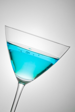 glass with blue cocktail tilted on grey background photo